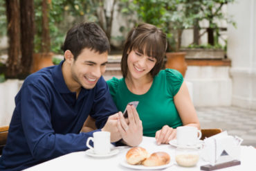 Couple at table on phone together